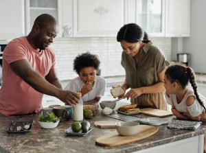 Mixed race family sits around the breakfast table together during Covid-19 to destress.