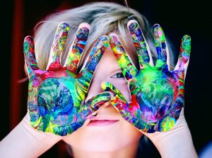 Young child with learning disabilities finger paints as a way to manage mental health issues.