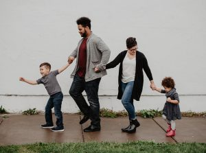 Parents of two small children walk holding hands as they practice positive parenting, connecting and bonding.