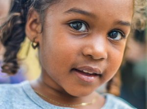 Young Black Girl looks with inquisitivity and wide eyes as she builds resilience and coping skills from family therapy