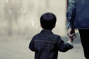 Small, highly sensitive child holding a parent's hand as viewed from behind