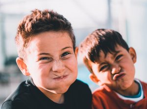 Teaching Kids Mindfulness: Two boys making funny faces as they hold their breaths in a mindfulness activity in family therapy