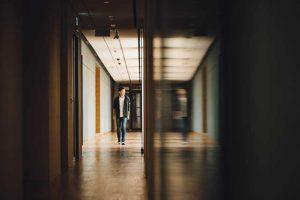 Dark hallway at school with LGBTQIA+ youth walking alone and a victim of bullying