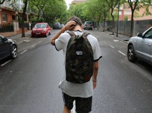 Teen boy walks down the street with backpack on, scratching the back of his head pondering creative expressive therapies.