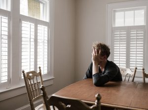 Distraught parent sits at kitchen table with his head in his hand distraught over a recent trauma.