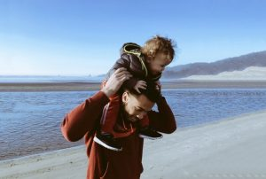 Single, divorcing father spends time at the beach with his son, carrying him on his shoulders.