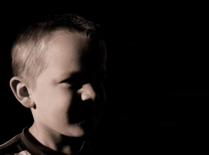 Small, caucasian boy with his face half shaded in the dark is a victim of child abuse.
