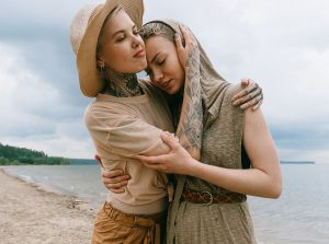 Two women on the beach comfort each other in times of sadness and depression