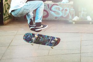 Teen in front of graffiti jumps on skateboard as a way to handle depression.