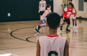 Middle school aged boy looks at a basketball court with stress from too many activiteis.