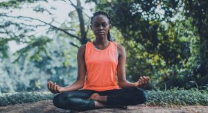 African American young woman sits yoga style for good mental health habits for 2021