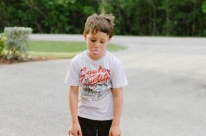 School aged caucasian boy pouts with shoulders down in a period of oppositional defiant disorder
